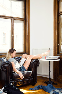 Mid adult woman relaxing on armchair reading a bookの写真素材 [FYI03608463]