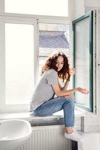 Young woman sitting on bathroom windowsillの写真素材 [FYI03608474]