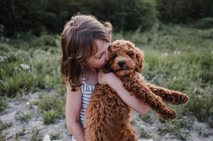 Girl kissing puppy in her armsの写真素材 [FYI03608562]