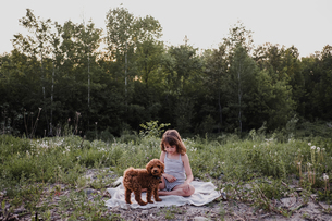 Girl and puppy on picnic blanketの写真素材 [FYI03608564]