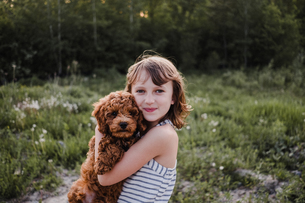 Girl posing with puppy in her armsの写真素材 [FYI03608565]