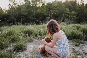 Girl kneeling to train puppyの写真素材 [FYI03608567]