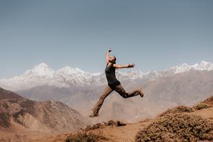Woman jumping on peak, Annapurna Circuit, the Himalayas, Dhaulagiri and Tukuche mountains in backgroの写真素材 [FYI03608635]