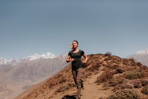 Woman jogging down from peak, Annapurna Circuit, the Himalayas, Muktinath, Nepalの写真素材 [FYI03608636]