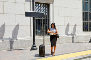 Businesswoman checking time on kerbの写真素材 [FYI03608680]