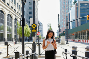 Businesswoman using cellphone by barriersの写真素材 [FYI03608691]