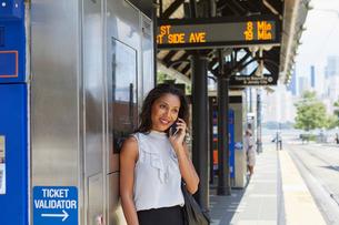 Businesswoman using cellphone by ticket machineの写真素材 [FYI03608697]