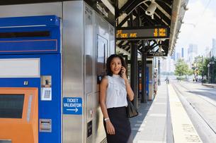 Businesswoman using cellphone by ticket machineの写真素材 [FYI03608699]