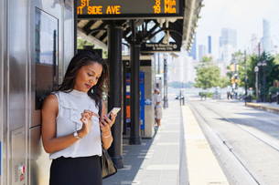 Businesswoman using cellphone by ticket machineの写真素材 [FYI03608701]