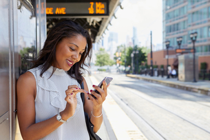 Businesswoman using cellphone in train stationの写真素材 [FYI03608702]