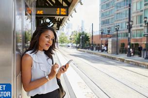 Businesswoman using cellphone by ticket machineの写真素材 [FYI03608706]