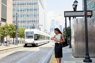 Businesswoman checking time by light rail lineの写真素材 [FYI03608723]