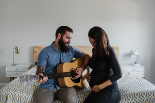 Man playing guitar to baby in wife's bellyの写真素材 [FYI03608865]