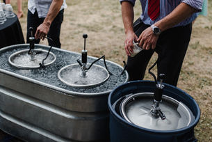 Men pouring beer from keg in cooling bath at barbecue, croppedの写真素材 [FYI03609001]