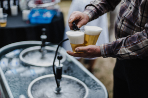 Man pouring beer from keg in cooling bath at barbecue, croppedの写真素材 [FYI03609003]