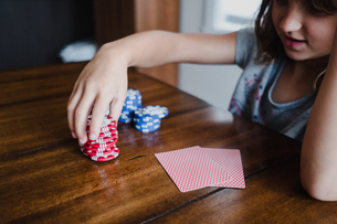 Girl playing cards at table, stacking gambling chips, close upの写真素材 [FYI03609005]