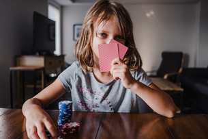 Girl hiding behind playing cards with gambling chips at table, portraitの写真素材 [FYI03609008]