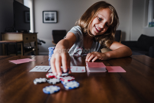 Girl playing cards at table, placing gambling chipsの写真素材 [FYI03609009]