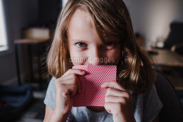 Girl hiding behind playing cards in living room, portraitの写真素材 [FYI03609010]