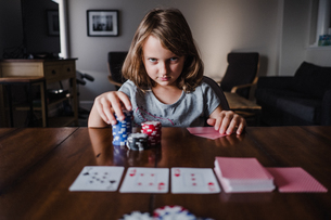 Girl with stack of gambling chips playing cards at table, portraitの写真素材 [FYI03609011]