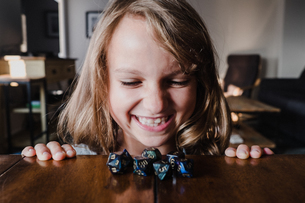 Smiling girl at table looking at role playing dice, close upの写真素材 [FYI03609013]