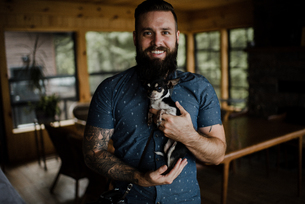 Young man holding pet dog in living room, portraitの写真素材 [FYI03609014]