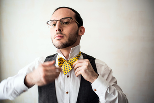 Businessman putting on bow tieの写真素材 [FYI03609062]