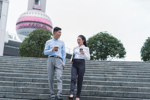 Young businesswoman and man with takeaway coffee moving down city stairway, Shanghai, Chinaの写真素材 [FYI03609088]