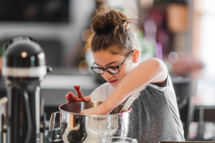 Girl putting ingredients into mixing bowl for christmas cookies at kitchen counterの写真素材 [FYI03609134]
