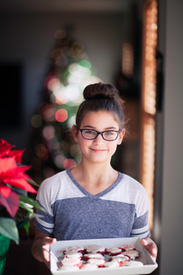 Girl holding tray of homemade christmas cookies in living room, portraitの写真素材 [FYI03609147]