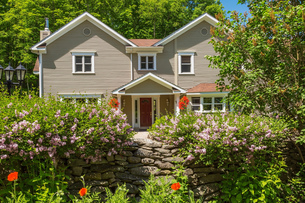 1990s Contemporary Victorian style country home facade with hanging baskets and dry stone wallの写真素材 [FYI03609164]