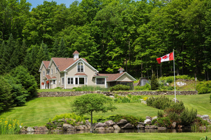 1990s Contemporary Victorian style country home with garden pond and Canadian flagの写真素材 [FYI03609165]