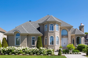 Facade of luxurious house in beige stone with front gardenの写真素材 [FYI03609171]