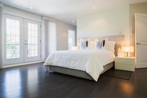 Master bedroom with queen size bed and dark wooden flooring, upstairs inside luxury residential homeの写真素材 [FYI03609176]