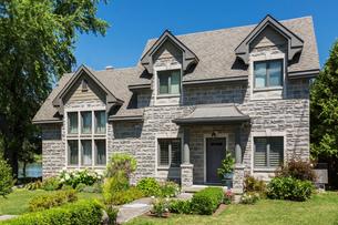 Facade of contemporary brick house facade with nuanced asphalt shingle roof and front gardenの写真素材 [FYI03609180]