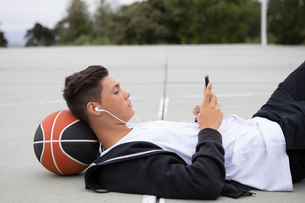 Male teenage basketball player lying on basketball court looking at smartphoneの写真素材 [FYI03609330]
