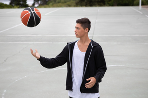 Male teenage basketball player on basketball court throwing and catching ballの写真素材 [FYI03609336]