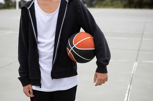 Male teenage basketball player on basketball court with ball under his arm, mid sectionの写真素材 [FYI03609337]
