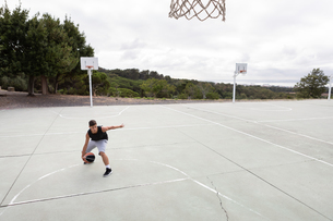 Male teenage basketball player practicing with ball near basketball hoopの写真素材 [FYI03609357]