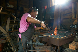 Blacksmith working in his forgeの写真素材 [FYI03609450]