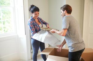Couple packing belongings into cardboard boxの写真素材 [FYI03609529]