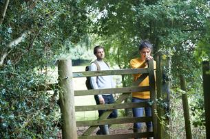 Hiker couple opening farm gateの写真素材 [FYI03609549]