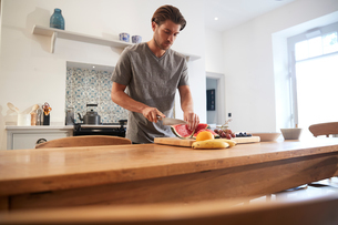 Young man slicing fresh watermelon at kitchen tableの写真素材 [FYI03609564]