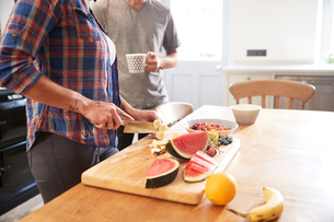 Couple slicing fresh fruit at kitchen table, mid sectionの写真素材 [FYI03609573]