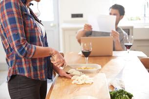 Woman preparing vegetables at kitchen table, boyfriend reading paperworkの写真素材 [FYI03609579]