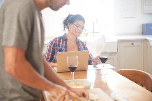 Man preparing vegetables at kitchen table, girlfriend reading paperworkの写真素材 [FYI03609580]