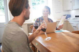 Couple at kitchen table drinking red wine while doing paperworkの写真素材 [FYI03609585]