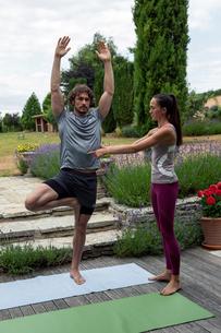 Female yoga teacher teaching young man yoga in garden, tree poseの写真素材 [FYI03609652]