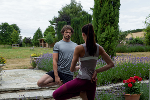 Man and woman practicing yoga in garden, tree poseの写真素材 [FYI03609653]