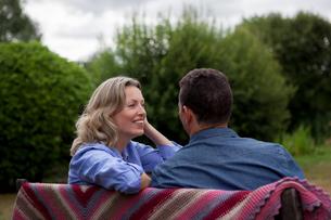 Mature couple sitting on garden benchの写真素材 [FYI03609671]